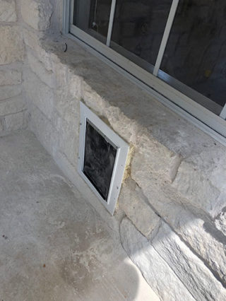 Cut a hole in through a wall made of rock to install a doggy door and tunnel