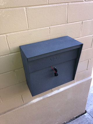 Wall made of cinder block (brick) with a mailbox mounted to the wall (1)