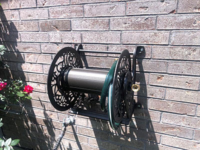 water hose holder mounted to a brick wall